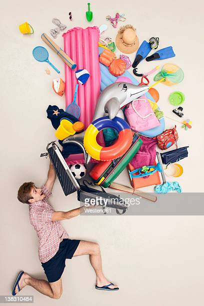 Germany, Artificial scene with man opening baggage full of beach toys