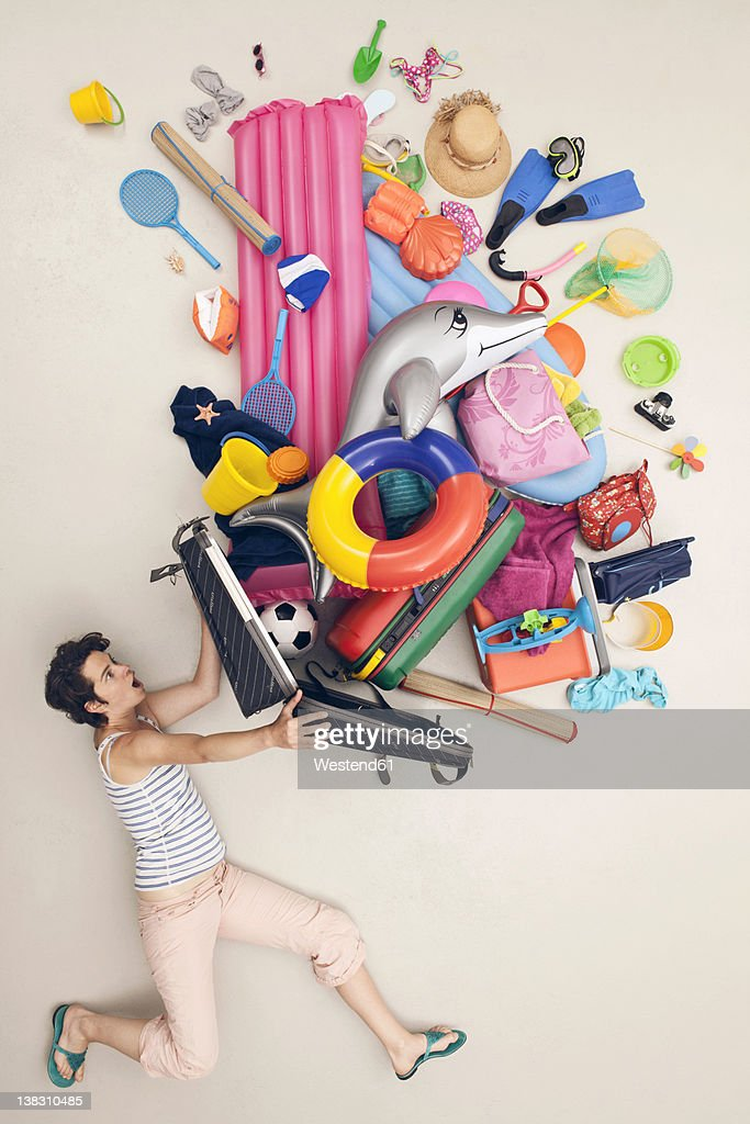 Germany, Artificial scene with woman opening baggage full of beach toys : Foto de stock
