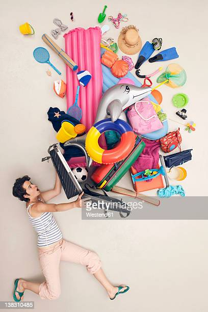 germany, artificial scene with woman opening baggage full of beach toys - bolsa objeto fabricado fotografías e imágenes de stock