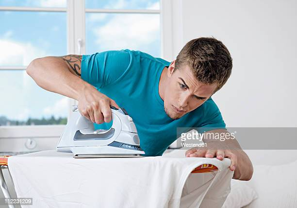 Germany, Augsburg, Man ironing shirt