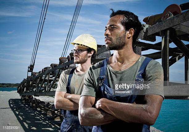 Germany, Augsburg, Two workers looking away with arms crossed