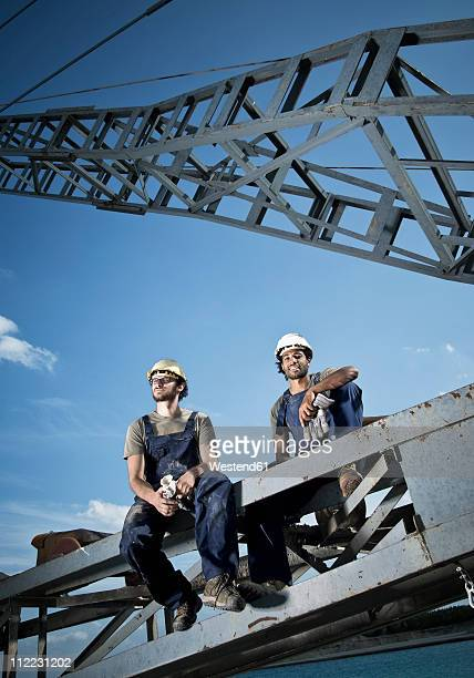 Germany, Augsburg, Two workers sitting on steel structure