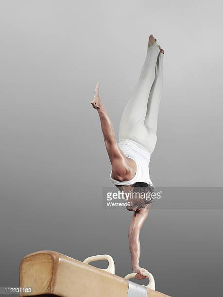 Germany, Augsburg, Young man doing headstand on pommel horse