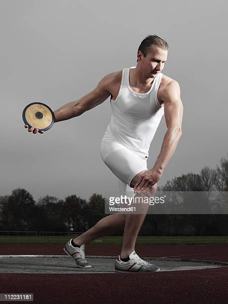 Germany, Augsburg, Young man holding discus