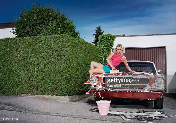 Germany, Augsburg, Young woman washing her vintage car