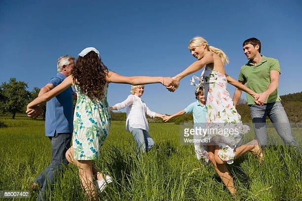 germany, baden württemberg, tübingen, three generation family dancing in meadow - baden württemberg stock photos and pictures
