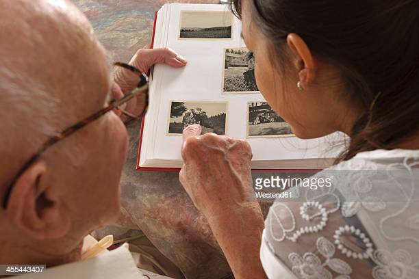 germany, baden wuerttemberg, grandfather and granddaughter looking photo ablum, close up - granddaughter stock photos and pictures