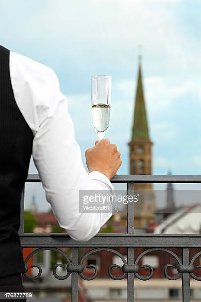 Germany, Baden-Wuerttemberg, Freiburg, woman with champagne glass, view from roof terrace