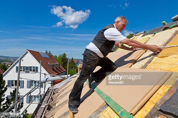 Germany, Baden-Wuerttemberg, Stuttgart, Mature man placing insulation
