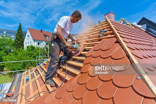 Germany, Baden-Wuerttemberg, Stuttgart, Mid adult man cutting roof tile
