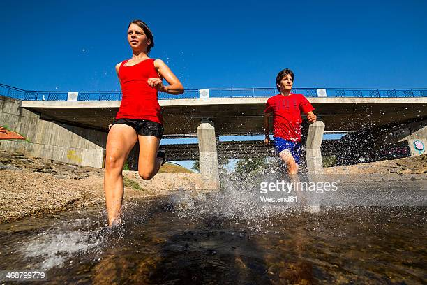 germany, baden-wuerttemberg, winterbach, athletic young man and young woman running through rems river - women in wet t shirts stock pictures, royalty-free photos & images
