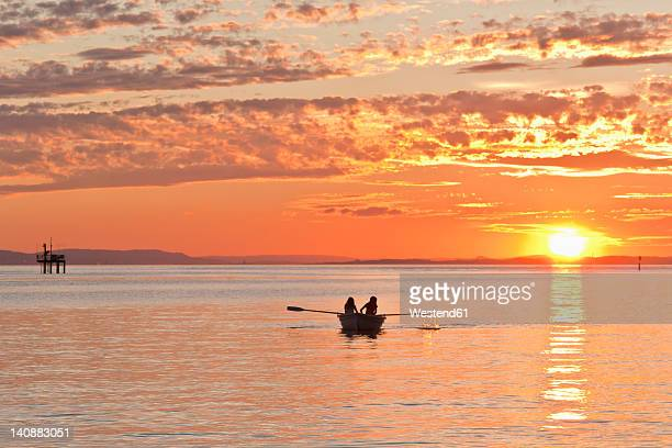 germany, baden-wurttemberg, langenargen, people in boat on lake constance at sunset - bodensee stock pictures, royalty-free photos & images