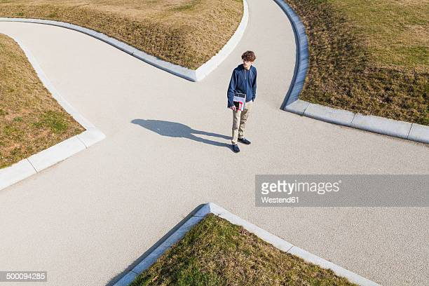 germany, baden-wurttemberg, teenage boy standing at crossing - beslissingen stockfoto's en -beelden