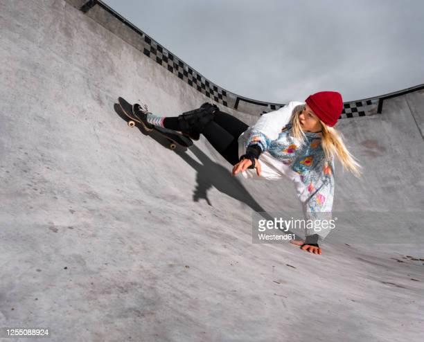 germany, baden-wurttemberg, waiblingen, young woman skateboarding in skate park - eislauf oder rollschuhlauf stock-fotos und bilder