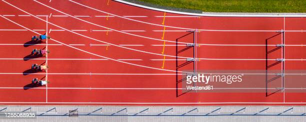 germany, baden-wurttemberg, winterbach, aerial view of female hurdlers kneelingon starting line - hurdling track event stock pictures, royalty-free photos & images
