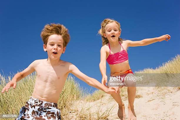 Germany, Baltic sea, boy and girl (6-9) jumping down beach dune