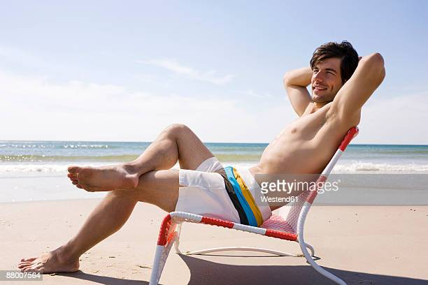 Germany, Baltic sea, man relaxing in chair on beach, side view