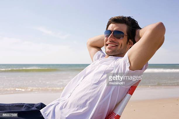 Germany, Baltic sea, man relaxing in chair on beach, smiling, portrait