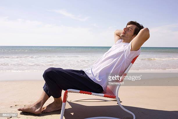 germany, baltic sea, young man on beach, portrait - outdoor chair stock pictures, royalty-free photos & images
