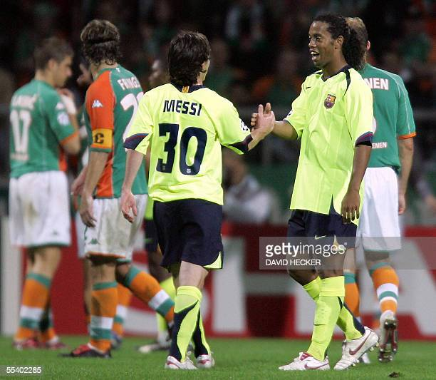 Barcelona's Brazilian midfielder Ronaldinho celebrates with Argentinian teammate Lionel Messi after they defeated Bremen 02 14 September 2005 at the...