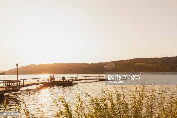 germany, bavaria, allgaeu, grosser alpsee, people on jetty at sunset - footbridge stock photos and pictures