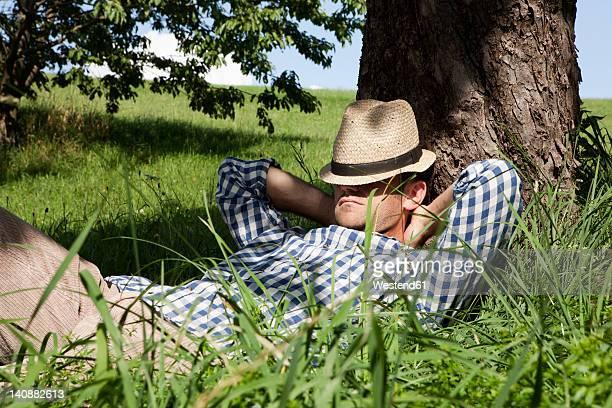 Germany, Bavaria, Altenthann, Man resting under tree