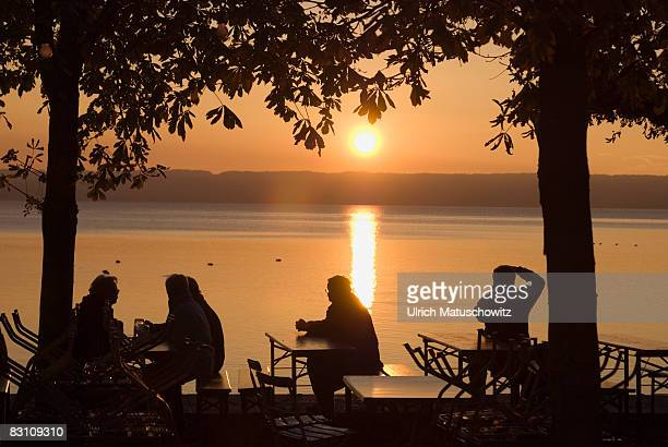 Germany, Bavaria, Ammersee, Silhouette of people in beer garden beside lake at sunset