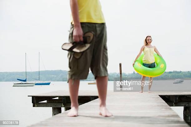 germany, bavaria, ammersee, couple on jetty, woman holding floating tire - partire bildbanksfoton och bilder