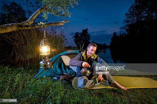 Germany, Bavaria, Ammersee, Man pouring drink near lakeshore while camping at night