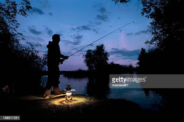 Germany, Bavaria, Ammersee, Man sitting near lakeshore with lantern and fishing at dusk