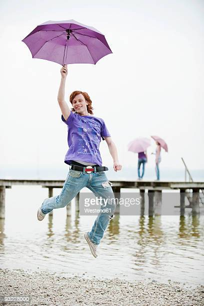 Germany, Bavaria, Ammersee, Young man holding umbrella and jumping,  teenage girls (16-17) in background