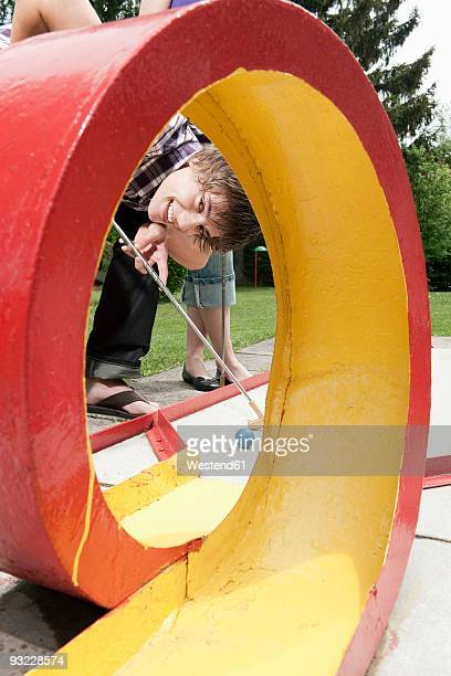 germany, bavaria, ammersee, young man playing mini golf - miniature golf stock photos and pictures