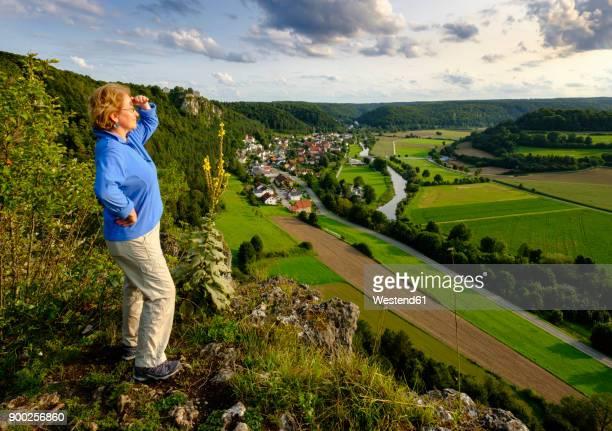 Germany, Bavaria, Arnsberg, Senior woman looking over Arnsberger Leite