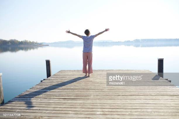 Germany, Bavaria, back view of woman standing on jetty at lake