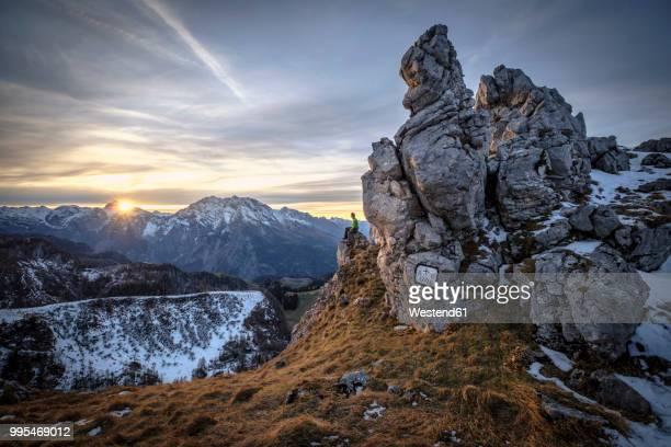 Germany, Bavaria, Berchtesgaden Alps, View to Schneibstein, hiker sitting on viewing point at sunset