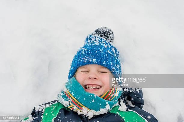 Germany, Bavaria, Berchtesgadener Land, happy boy lying in snow