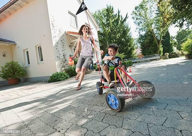 Germany, Bavaria, Boy driving pedal go kart and woman running with family in background