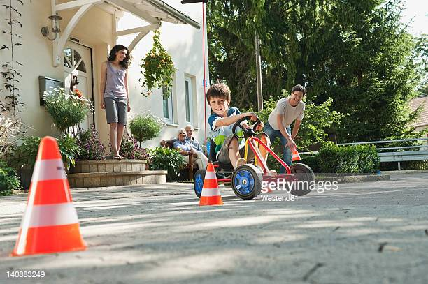 Germany, Bavaria, Boy driving pedal go kart with family in background