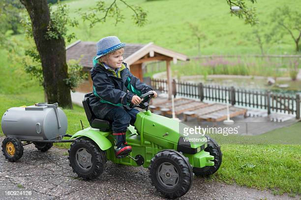 Germany, Bavaria, Boy sitting in toy tractor with trailer