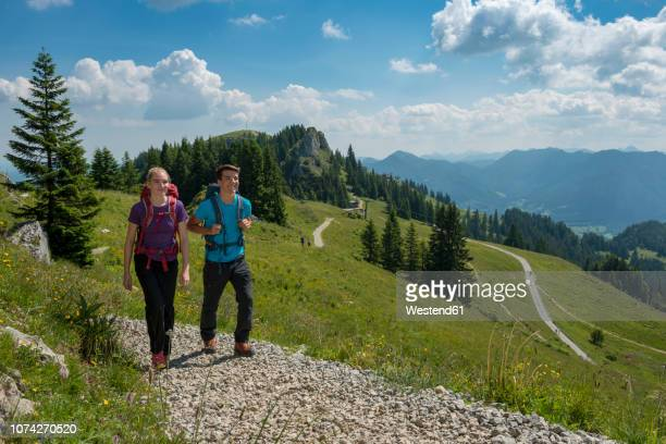 germany, bavaria, brauneck near lenggries, young couple hiking in alpine landscape - lenggries stock pictures, royalty-free photos & images