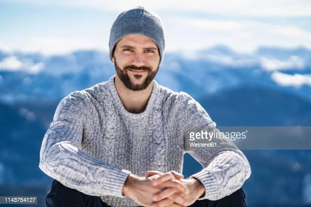 germany, bavaria, brauneck, portrait of smiling man in winter in the mountains - bonnet de laine photos et images de collection