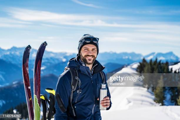 germany, bavaria, brauneck, portrait of smiling man on a ski tour in winter in the mountains having a break - スキー板 ストックフォトと画像