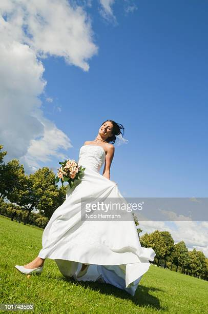Germany, Bavaria, Bride holding bouquet running in park, smiling