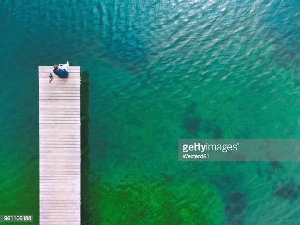 germany, bavaria, chiemsee, man sitting on jetty - jetty stock pictures, royalty-free photos & images