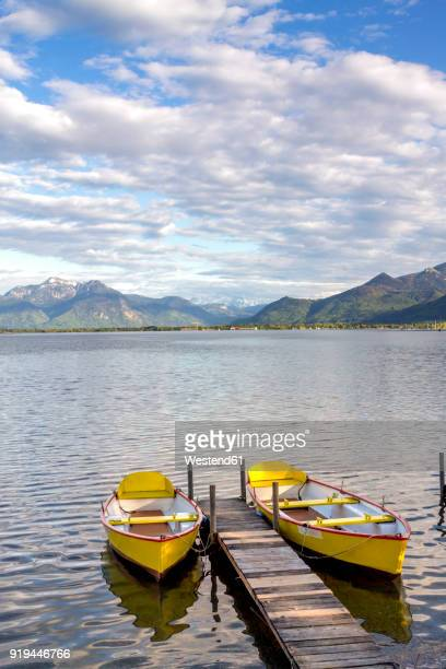 Germany, Bavaria, Chiemsee, Prien am Chiemsee, yellow rowing boats at boardwalk