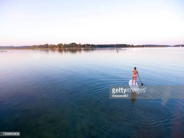germany, bavaria, chiemsee, woman on sup board - lakeshore stock pictures, royalty-free photos & images