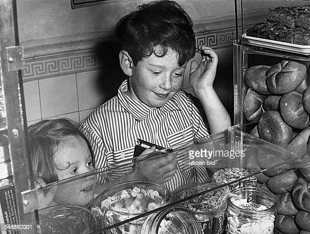 Germany Bavaria children at the baker's looking at sweets 1950s