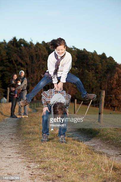 Germany, Bavaria, Children playing leapfrog and parents standing in background
