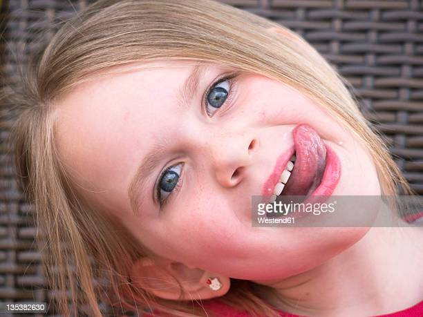 germany, bavaria, close up of girl teasing, portrait - little girl sticking out tongue stock photos and pictures
