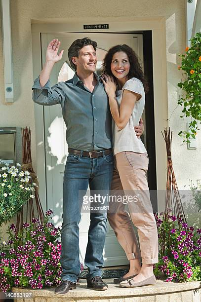germany, bavaria, couple at entrance of house, smiling - waving gesture stock photos and pictures